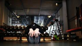 Muchacha morena atlética atractiva que hace estirar mientras que se sienta en una estera de los deportes en el gimnasio almacen de metraje de vídeo