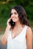 Muchacha morena atractiva con el móvil Foto de archivo libre de regalías