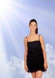 Muchacha morena atractiva con el vestido negro que mira para arriba Fotografía de archivo