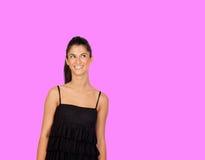 Muchacha morena atractiva con el vestido negro que mira para arriba Foto de archivo libre de regalías