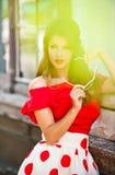 Muchacha morena atractiva con la presentación roja de la blusa y de las gafas de sol al aire libre Mujer joven de moda hermosa co Fotografía de archivo libre de regalías