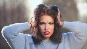 Muchacha morena atractiva del primer con el pelo hermoso y actitudes rojas de los labios en la cámara que representa diversas emo metrajes