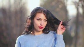 Muchacha morena atractiva del primer con el pelo hermoso y actitudes rojas de los labios en la cámara que representa diversas emo almacen de video