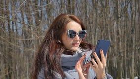 Muchacha morena atractiva en sunglesses de moda que llama alguien que usa aire libre azul del smartphone en el parque en árboles metrajes