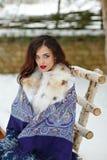 Muchacha morena atractiva hermosa en una bufanda azul en el fondo o Fotos de archivo