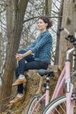Muchacha morena atractiva que se sienta en árbol viejo enorme Imágenes de archivo libres de regalías