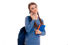 Muchacha morena bastante joven del estudiante con el teléfono que habla de la mochila azul aislado en el fondo blanco Imagen de archivo