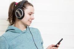 Muchacha morena blanca joven con el jugador y en auriculares que escucha la música de danza en fondo de la casa ligera Imagen de archivo