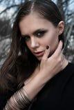 Muchacha morena bonita con maquillaje brillante y labios púrpuras que llevan la presentación negra al aire libre en el cielo azul Imagen de archivo