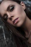 Muchacha morena bonita con maquillaje brillante y labios púrpuras que llevan la presentación negra al aire libre en el cielo azul Fotos de archivo libres de regalías
