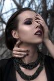 Muchacha morena bonita con maquillaje brillante y labios púrpuras que llevan la presentación negra al aire libre en el cielo azul Foto de archivo