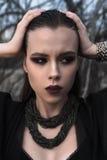 Muchacha morena bonita con maquillaje brillante y labios púrpuras que llevan la presentación negra al aire libre en el cielo azul Fotos de archivo