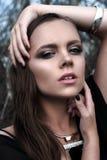 Muchacha morena bonita con maquillaje brillante y labios púrpuras que llevan la presentación negra al aire libre en el cielo azul Imagen de archivo libre de regalías