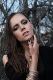 Muchacha morena bonita con maquillaje brillante y labios púrpuras que llevan la presentación negra al aire libre en el cielo azul Foto de archivo libre de regalías