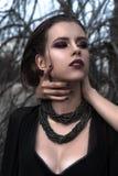 Muchacha morena bonita con maquillaje brillante y labios púrpuras que llevan la presentación negra al aire libre en el cielo azul Imágenes de archivo libres de regalías