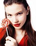 Muchacha morena bonita joven con el caramelo rojo que presenta en el backgr blanco Imágenes de archivo libres de regalías