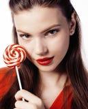 Muchacha morena bonita joven con el caramelo rojo que presenta en el fondo blanco aislado Imagenes de archivo