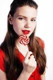 Muchacha morena bonita joven con el caramelo rojo que presenta en el fondo blanco aislado Fotografía de archivo