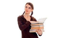 Muchacha morena bonita joven del estudiante en ropa marrón del deporte con las coletas y los libros en sus manos que parecen lejo Foto de archivo libre de regalías