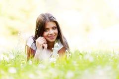 Muchacha morena bonita que pone en hierba Fotografía de archivo