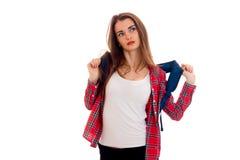 Muchacha morena cansada elegante del estudiante con la mochila azul que parece ausente y que presenta en la cámara aislada en el  Fotografía de archivo