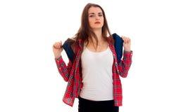 Muchacha morena cansada joven del estudiante con la mochila en sus hombros que presentan y que miran la cámara aislada en blanco Imagen de archivo