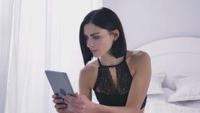 Muchacha morena caucásica atractiva joven en la ropa interior negra usando una tableta, mirada descontentada, fps blancos del fon almacen de metraje de vídeo