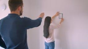 Muchacha morena caucásica que cuelga la imagen enmarcada en la pared blanca mientras que su novio ordena el lugar correcto para é almacen de video