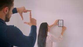 Muchacha morena caucásica que elige el lugar para la imagen enmarcada en la pared blanca mientras que su novio hace forma del mar almacen de metraje de vídeo