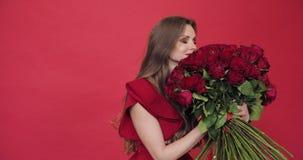 Muchacha morena con el pelo largo en flores de torneado de la blusa roja almacen de metraje de vídeo