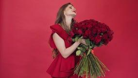 Muchacha morena con el pelo largo en flores de torneado de la blusa roja almacen de video