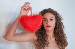 Muchacha morena con el pelo rizado, con el corazón para el día del ` s de la tarjeta del día de San Valentín Foto de archivo