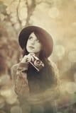 Muchacha morena con la cámara en el parque Imagenes de archivo
