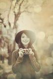 Muchacha morena con la cámara en el parque Imagen de archivo