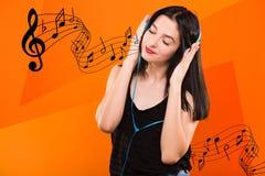 Muchacha morena con los auriculares azules y con las notas musicales Imagen de archivo libre de regalías