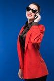 Muchacha morena con un teléfono en su mano Imagenes de archivo