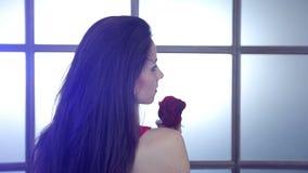 Muchacha morena con una rosa roja Luz azul en el pelo almacen de video