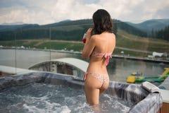 Muchacha morena de la visión trasera en el cóctel de consumición del bikini, colocándose en el Jacuzzi al aire libre el vacacione fotografía de archivo libre de regalías