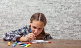 Muchacha morena del adolescente joven con el pelo largo que dibuja con el cepillo en una tabla en fondo gris de la pared con el e imagenes de archivo