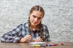 Muchacha morena del adolescente joven con el pelo largo que dibuja con el cepillo en una tabla en fondo gris de la pared con el e imágenes de archivo libres de regalías