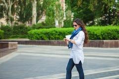 Muchacha morena del negocio hermoso que camina abajo de la calle con el ordenador portátil Imágenes de archivo libres de regalías