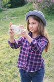 Muchacha morena del niño del tweenie pre-adolescente adorable con su smartphone en el parque de la primavera Imagenes de archivo
