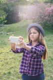 Muchacha morena del niño del tweenie pre-adolescente adorable con su smartphone en el parque de la primavera Foto de archivo