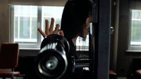 Muchacha morena deportiva joven que consigue lista para hacer ejercicios en una posición en cuclillas con un barbell Entrenamient almacen de video