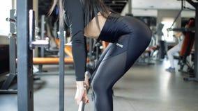 Muchacha morena deportiva joven que hace el deadlift con un barbell en el gimnasio Muchacha de la aptitud metrajes