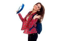 Muchacha morena divertida joven del estudiante con la mochila en sus hombros que sonríe en la cámara aislada en el fondo blanco Imagen de archivo libre de regalías