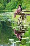 Muchacha morena en el puente sueco del lago con la reflexión del agua Foto de archivo
