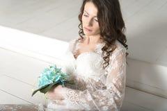 Muchacha morena en el vestido blanco que se sienta en las escaleras Imágenes de archivo libres de regalías