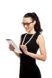 Muchacha morena en el vestido negro que lleva a cabo el ipad Imagen de archivo
