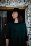 Muchacha morena en negro con un sombrero elegante y una puerta de madera vieja Imagenes de archivo